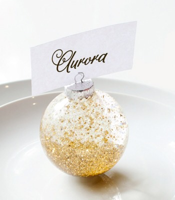 Confetti Snow Globe Place Card Holder  Gold glitter snows in this globe placecard holder.  TOOLS AND SUPPLIES clear plastic ornament wire cutters glue gun and glue glycerin water coarse glitter small confetti white sticky tack